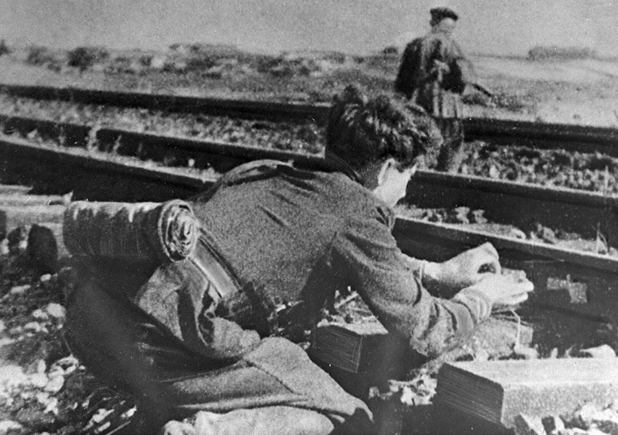 Подрывник бригады Народные мстители закладывает взрывчатку под рельсы